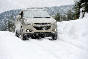 image of suv driving on snow packed mountain road